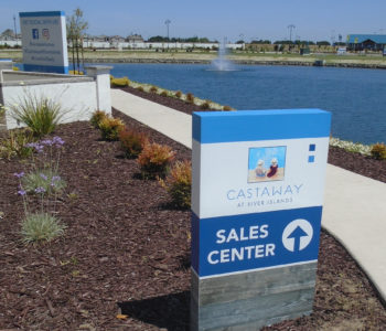 Rectangular sign located in the front lawn with an arrow pointing to a Sales Center.