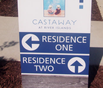 Blue and white way-finding sign directing traffic to various residences.