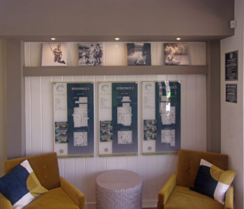 Interior wall with 2 seating chairs & end table. Behind them a display of 3 models on printed flat acrylic. Lifestyle photos displayed on bookshelf above.